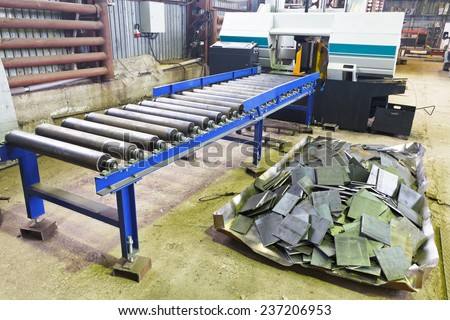 two-column band saw machine for vertical cuts with feeder and cutting metal tile in mechanical workshop - stock photo