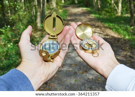 Two compasses in the hands - stock photo