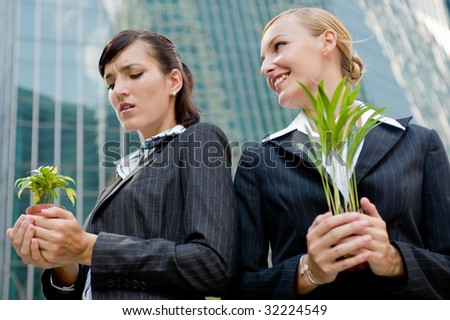 Two competitive businesswomen cupping their plants in their hands - stock photo