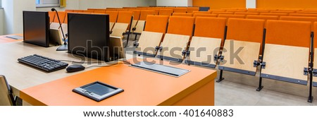 Two computers on desk in modern lecture hall in new college building. Orange chairs and grey floor - stock photo