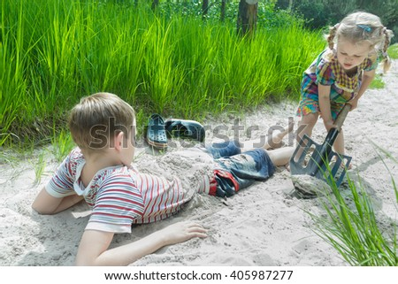 Two concentrated siblings playing on beach dune and burying each other in white sand at pinewood background - stock photo