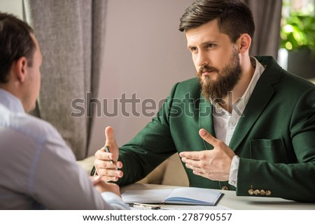 Two confident businessmen sitting at the table and discussing contract. - stock photo