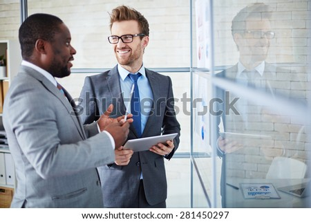 Two confident colleagues sharing ideas at meeting in office - stock photo