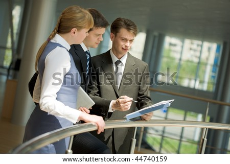 Two confident partners listening to smart man sharing his ideas - stock photo