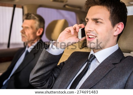 Two confident successful businessmen at a meeting sitting in the luxurious car. - stock photo