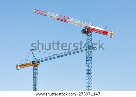 Two construction cranes are on a clear blue sky. Modern beautiful cranes view from below. Blue with yellow and red with white. Clear sunny day. - stock photo