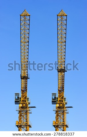 Two construction tower cranes isolated on blue sky background, synchronously parallel standing yellow objects  - stock photo