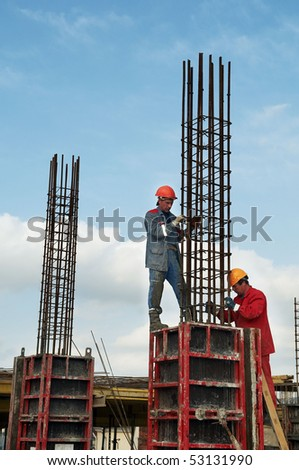 two construction workers installing reinforcement for concrete - stock photo