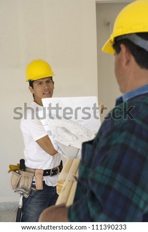 Two construction workers with blueprint at workplace - stock photo