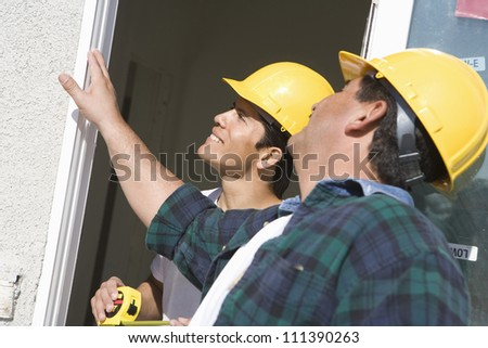 Two construction workers with measure tape standing near window - stock photo
