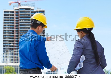 Two contractors, man and woman facing the building project in progress - stock photo