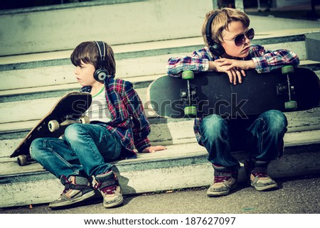 two cool skaters resting on stairs, vintage effect added - stock photo