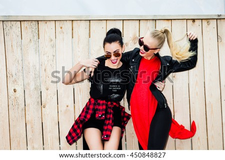 Two cool trendy bold girl in casual black and red clothes, laughing, going crazy on the wooden background, blonde and brunette. Stylish hairstyle and Makeup. Vogue Style. Fashion Beauty Swag Girl. - stock photo