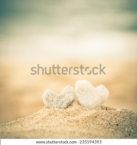 two coral hearts on a beach in instagram effect - stock photo