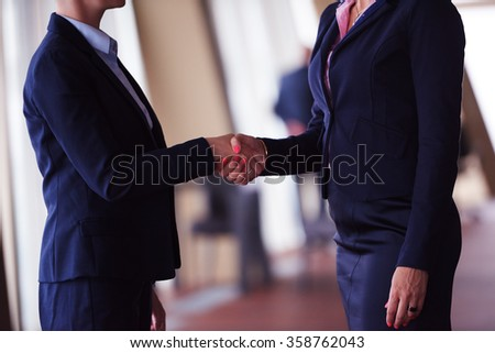 two corporate business woman at modern bright office interior make deal and handshake - stock photo