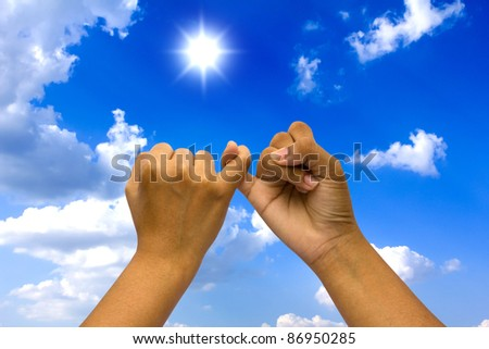 Two coupled hands on blue sky. - stock photo