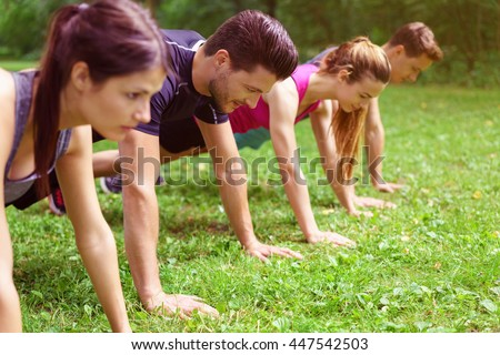 Two couples doing crossfit exercises performing push-ups in the planking position on green grass outdoors in a park - stock photo