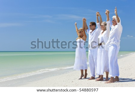 Two couples, generations of a family together holding hands and racing their arms in celebration on a deserted tropical beach - stock photo
