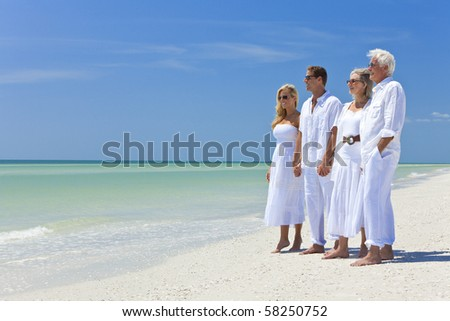 Two couples, generations of a family together holding hands on a tropical beach - stock photo