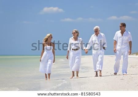 Two couples, generations of a family together walking and holding hands on a tropical beach - stock photo