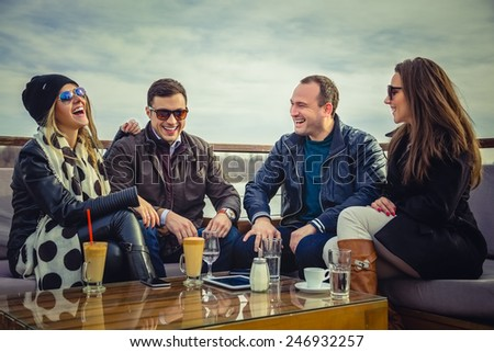 Two couples laughing outdoors - stock photo