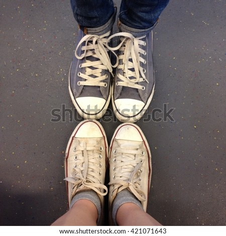 Two couples of teenagers feet in sneakers standing on grid face to face great for any use. - stock photo