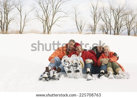 Two couples wearing snowshoes - stock photo