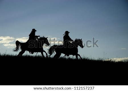 Two cowboys silhouetted against a Montana dawn sky - stock photo