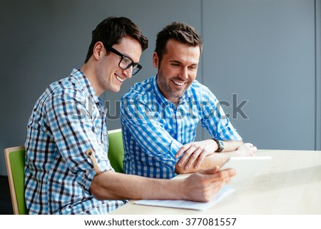 Two coworkers looking at tablet during business meeting - stock photo