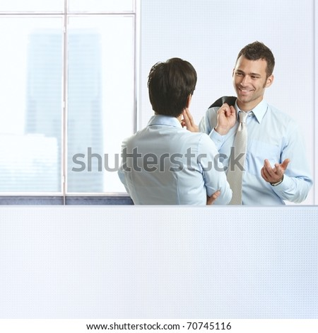 Two coworkers standing chatting in business office, smiling. - stock photo