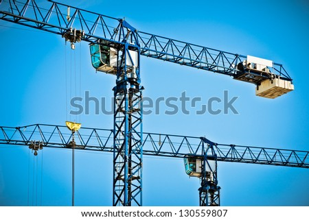 Two cranes and blue sky - stock photo