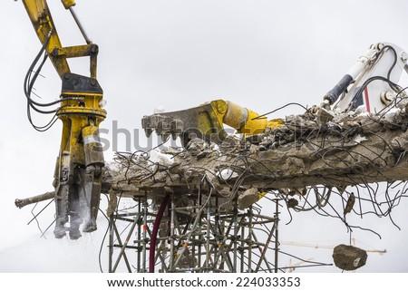 Two cranes breaking down a bridge en la plaza de Les Glories, Barcelona. - stock photo