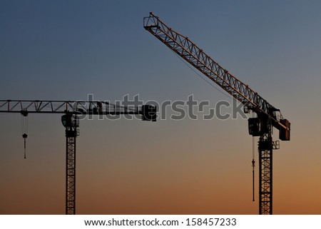 Two cranes work at a decline - stock photo