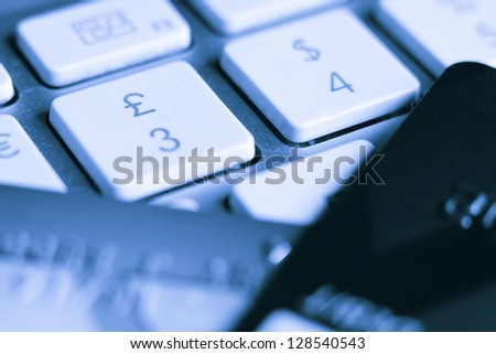 Two credit cards next to the pound and dollar keys on a computer keyboard - stock photo