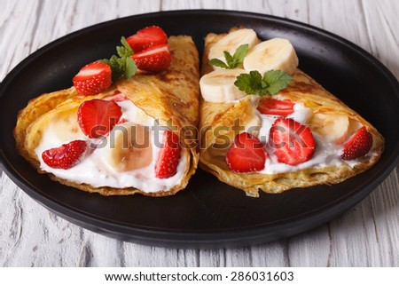 Two crepes with fresh strawberries, bananas and cream close-up on a plate. horizontal  - stock photo
