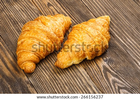 Two croissant on a background of the old wooden table. - stock photo