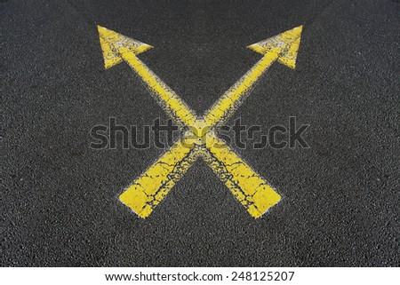 Two crossed yellow arrows painted on a road - stock photo
