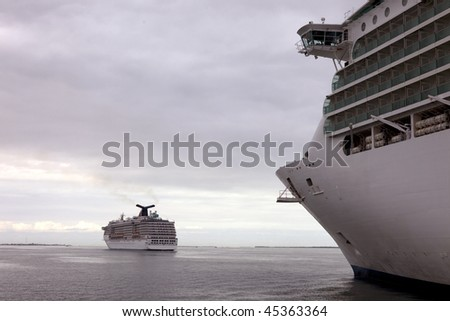 two cruise ships sailing at sea in tandem under cloudy sky - stock photo