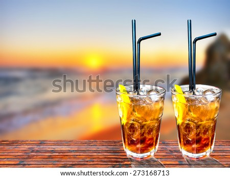 Two Cuba libre exotic tasty cocktail with beautiful sunset background - stock photo