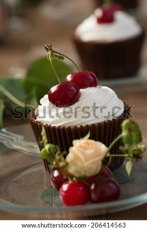 Two cupcake with whipped cream and cherries on wooden table, shallow DOF. - stock photo