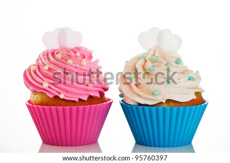 Two cupcakes in a pink and blue baking cups with pink and white cream, with decoration and two heart on the top on white background as a studio shoot - stock photo