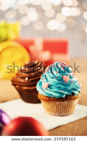 Two cupcakes - shallow DOF. Christmas lights and gifts in the background. - stock photo