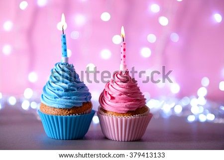 Two cupcakes with candle on a glitter background - stock photo