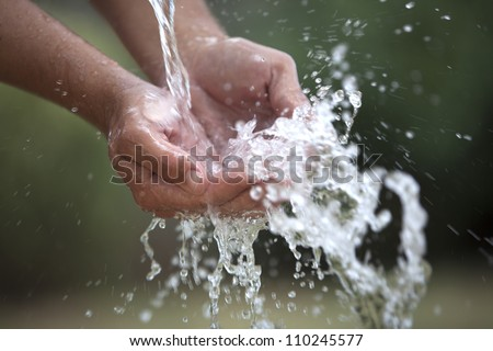Two cupped hands feel the water spashing into them gently. - stock photo