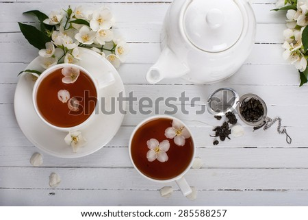Two cups and a teapot of green tea with jasmine on a white surface - stock photo