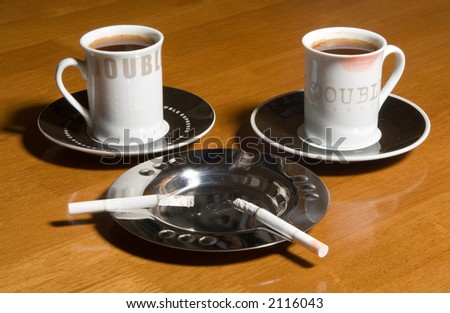 Two cups of coffee and two cigarettes on a table - stock photo
