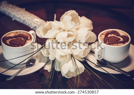 Two cups of coffee and white tulips - stock photo