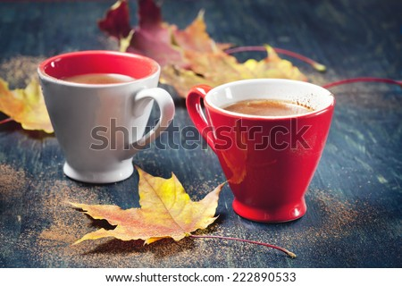Two cups of coffee with autumn leaves, on wooden background, selective focus. - stock photo