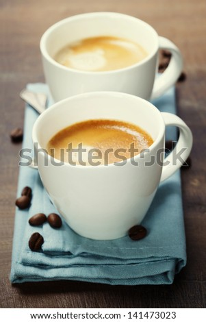 two cups of coffee with blue napkin - stock photo