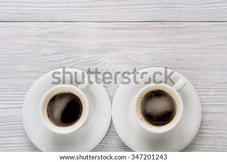 Two cups of coffee with foam on a white wooden table. Top view. Copy space. - stock photo